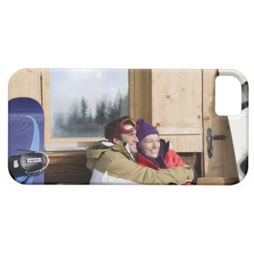 Mid adult couple embracing outside log cabin iPhone 5 case