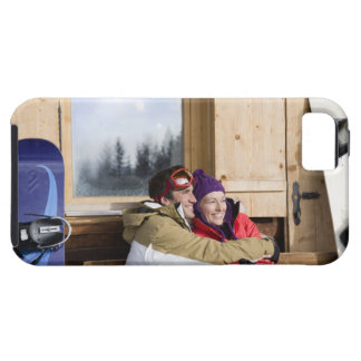 Mid adult couple embracing outside log cabin iPhone 5 covers