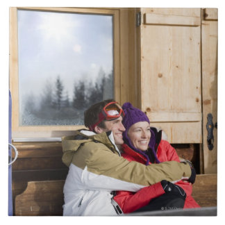 Mid adult couple embracing outside log cabin large square tile