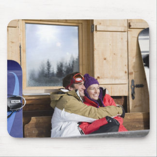 Mid adult couple embracing outside log cabin mouse pad