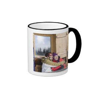 Mid adult couple embracing outside log cabin coffee mugs