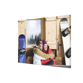 Mid adult couple embracing outside log cabin stretched canvas prints