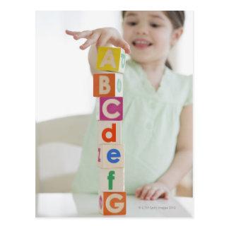 Mixed race girl stacking alphabet blocks postcard