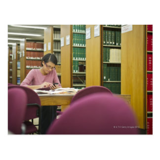Mixed race woman doing research in library 2 postcard