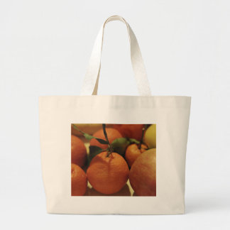 Oranges apples fruit on a table tote bags
