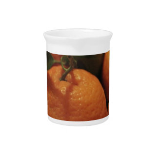 Oranges apples fruit on a table drink pitcher