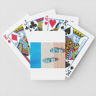 Pair of slippers at edge of swimming pool bicycle playing cards