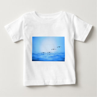 Pelicans flying over ocean baby T-Shirt