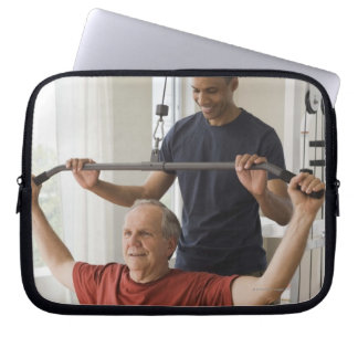 Personal trainer with man in home gym laptop sleeve