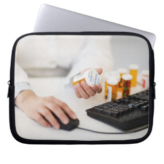 Pharmacist with pill bottles at computer laptop sleeve