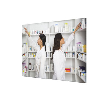 Pharmacists reaching for medication on shelves stretched canvas prints
