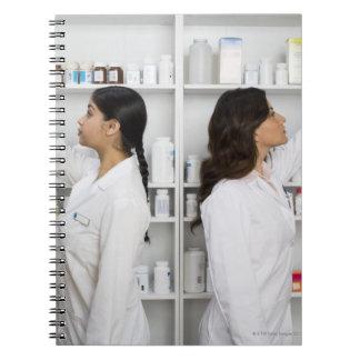 Pharmacists reaching for medication on shelves spiral notebooks