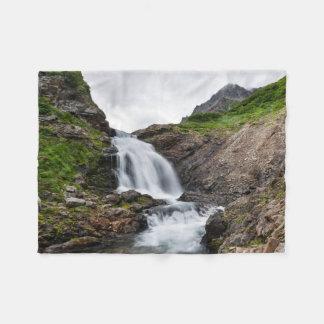 Picturesque waterfall in mountain range fleece blanket
