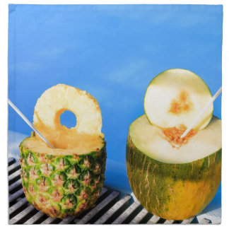 Pineapple and melon fruit with straws at pool napkin