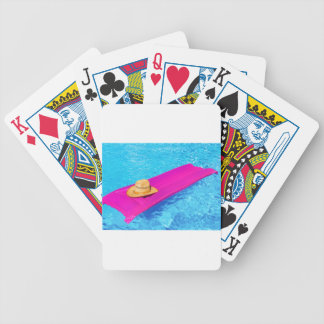 Pink air mattrass with hat in swimming pool bicycle playing cards