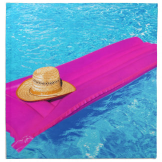 Pink air mattrass with hat in swimming pool napkin