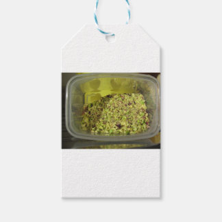 Raw chopped pistachios in a plastic food pan gift tags