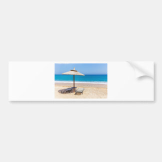 Reed beach umbrella with loungers on beach at sea. bumper sticker