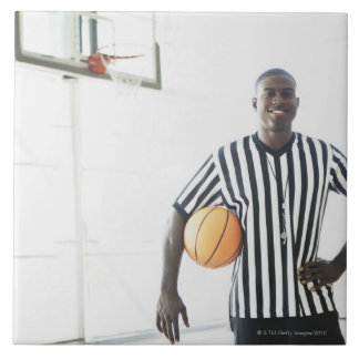Referee holding basketball on court ceramic tiles