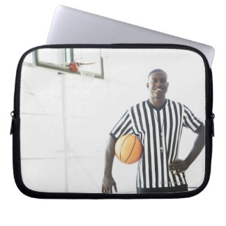 Referee holding basketball on court computer sleeve