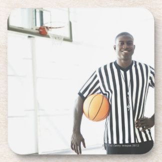 Referee holding basketball on court coasters