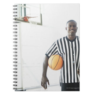 Referee holding basketball on court notebook