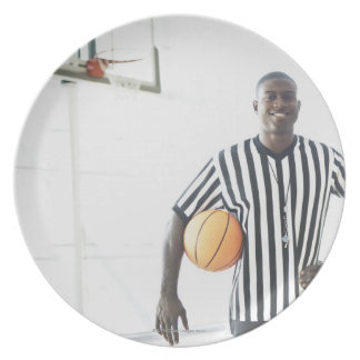Referee holding basketball on court dinner plate
