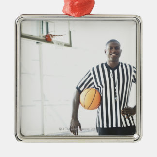 Referee holding basketball on court Silver-Colored square decoration