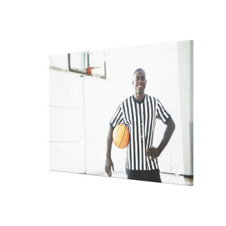 Referee holding basketball on court stretched canvas print