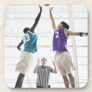 Referee watching basketball players jumping beverage coasters