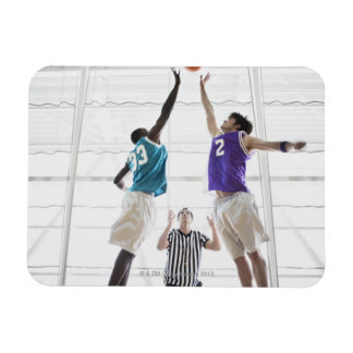 Referee watching basketball players jumping rectangle magnets