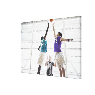 Referee watching basketball players jumping gallery wrapped canvas