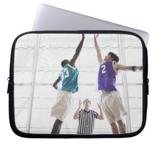 Referee watching basketball players jumping laptop computer sleeve