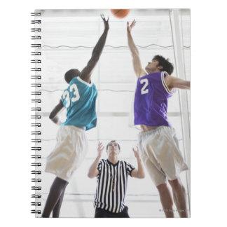 Referee watching basketball players jumping note books