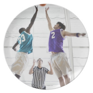 Referee watching basketball players jumping dinner plate