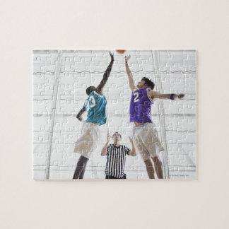 Referee watching basketball players jumping puzzles