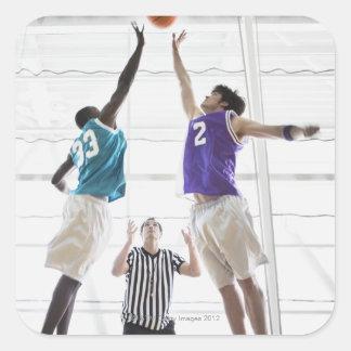 Referee watching basketball players jumping square sticker