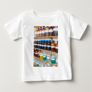 Rows of fluid chemicals in bottles at chemistry baby T-Shirt