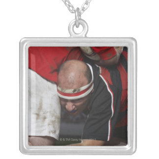 Rugby player tacking opponent, mid section silver plated necklace