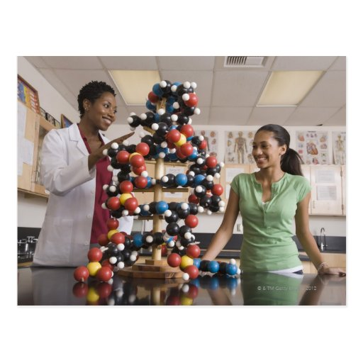 Science teacher and teenage girl looking at post card