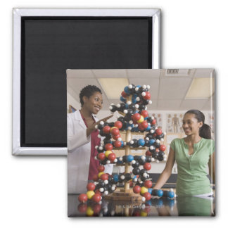 Science teacher and teenage girl looking at square magnet