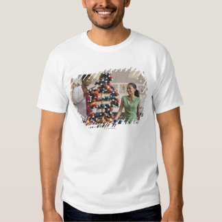 Science teacher and teenage girl looking at t shirt