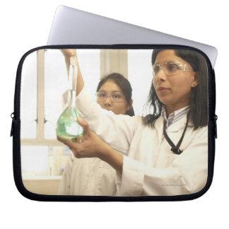 Scientist adding solution to beaker laptop sleeve