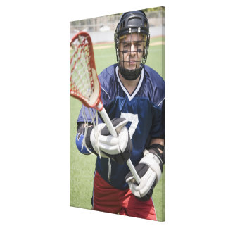 Serious lacrosse player holding crosse canvas print