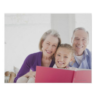 Smiling grandparents reading cookbook with poster