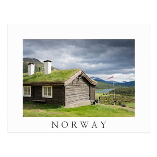 Sod roof log cabin in Norway white text postcard