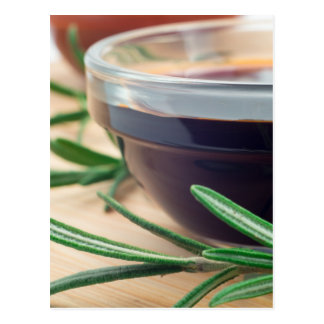 Soy sauce in a glass and a sprig of rosemary postcard