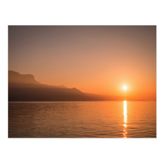 Sunset over water orange gold mountains postcard