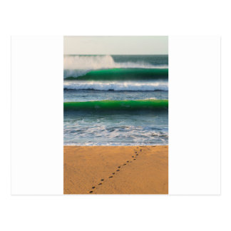 Surfer footprints on sand beach and green waves postcard