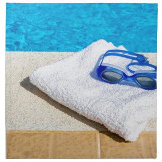 Swimming goggles and towel near swimming pool napkin